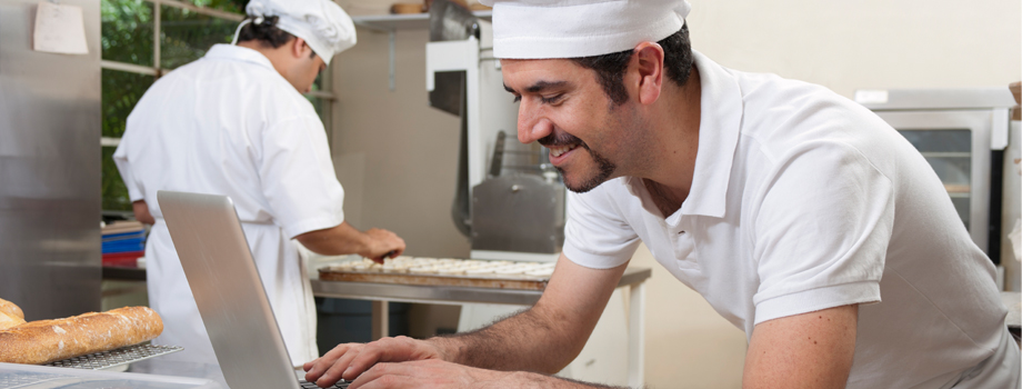 Chef  leaning at table at computer